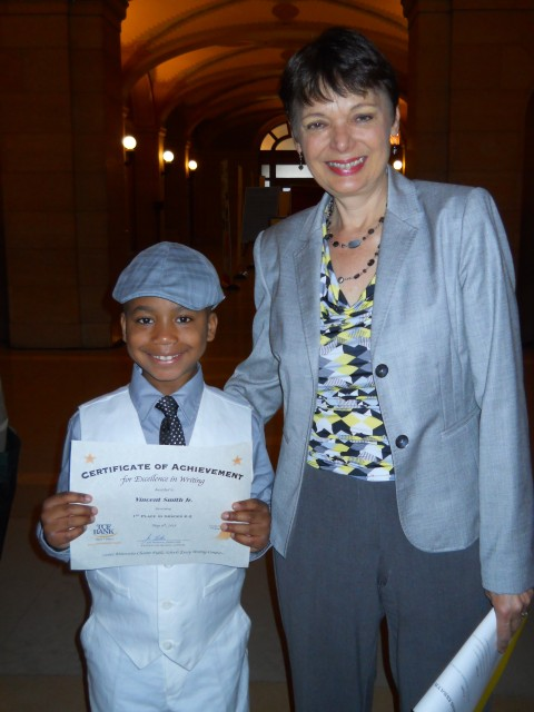 K-2 first place winner Vincent Smith Jr. (Urban Academy 2nd Garde) poses for a photo with Senator Sandra L. Pappas (DFL) District 65.